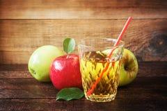 Vidrio de zumo de manzana con las manzanas rojas y verdes en fondo de madera Fotografía de archivo