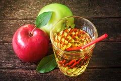 Vidrio de zumo de manzana con las manzanas rojas y verdes en fondo de madera imagenes de archivo