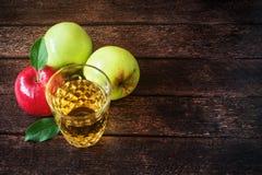 Vidrio de zumo de manzana con las manzanas rojas y verdes en fondo de madera foto de archivo libre de regalías