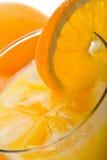 Vidrio de zumo de naranja con los cubos de hielo Fotografía de archivo