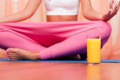 Vidrio de zumo de naranja delante de la mujer deportiva Fotografía de archivo libre de regalías