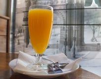 Vidrio de zumo de naranja en la mesa de centro imagenes de archivo