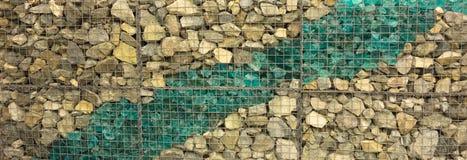 Vidrio decorativo del mar mezclado con la piedra incluida en una jaula del alambre foto de archivo