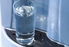 Vidrio del agua y del dispensador Imagenes de archivo
