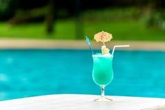 Vidrio del cóctel azul en la piscina en tiempo de verano Imagen de archivo