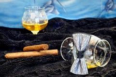 Vidrio del coñac con un cigarro, corbata de lazo en un terciopelo negro con un contexto azul Foto de archivo libre de regalías
