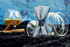 Vidrio del coñac con un cigarro, corbata de lazo en un terciopelo negro con un contexto azul Imagen de archivo libre de regalías