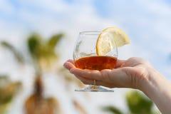 Vidrio del coñac con una rebanada de limón en una mano del ` s de la mujer contra el cielo azul y las palmeras imágenes de archivo libres de regalías
