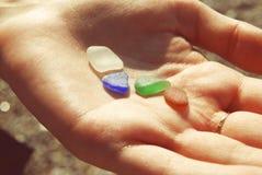Vidrio del color en una mano de la muchacha en la playa Imágenes de archivo libres de regalías