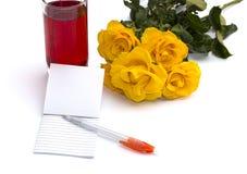 Vidrio del jugo, del cuaderno con la manija y de un ramo de rosas Foto de archivo