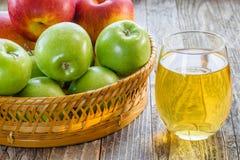Vidrio del jugo y de la cesta con las manzanas Fotos de archivo