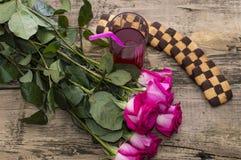 Vidrio del jugo y del ramo de rosas, aún vida encendido Fotografía de archivo