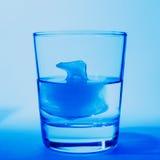 Vidrio del primer del agua potable en un fondo azul aislado con hielo bajo la forma de oso polar Imagen de archivo