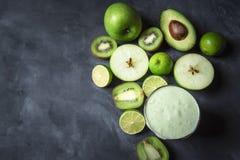 Vidrio del Smoothie y frutas verdes en la tabla de cocina Dieta sana f foto de archivo