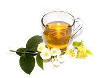 Vidrio del té de la cal adornado con las flores Imagen de archivo libre de regalías