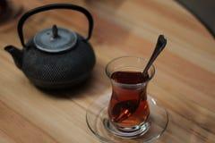 Vidrio del té negro con la cuchara y de la caldera en la tabla de madera Foto de archivo