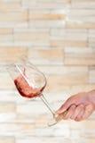 Vidrio del tema del vino por una mano en un movimiento circular Imagen de archivo libre de regalías