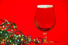 Vidrio del tulipán de cerveza con las luces de la Navidad Imagen de archivo