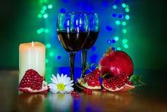 Vidrio del vino rojo, de la granada madura, de la flor blanca, y de la vela ardiendo Imagenes de archivo