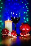 Vidrio del vino rojo, de la granada madura, y de la vela ardiendo Fotografía de archivo libre de regalías