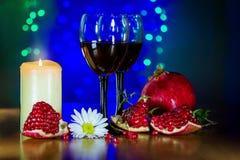 Vidrio del vino rojo, de la granada madura, y de la vela ardiendo Foto de archivo libre de regalías