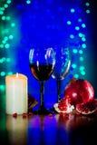 Vidrio del vino rojo, de la granada madura, y de la vela ardiendo en la tabla Imagen de archivo libre de regalías