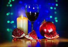 Vidrio del vino rojo, de la granada madura, y de la vela ardiendo en la tabla Foto de archivo