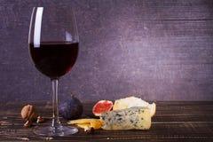 Vidrio del vino rojo, del queso, de la uva, de nueces, de higos, de ciruelos y de la manzana en fondo de madera Imagenes de archivo