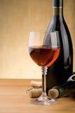 Vidrio del vino rojo y de la botella con la uva en la madera Fotos de archivo