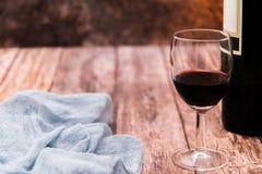 Vidrio del vino rojo y de la botella en la tabla de madera con el espacio de la copia Fotografía de archivo