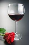 Vidrio del vino rojo y de la flor color de rosa Fotografía de archivo