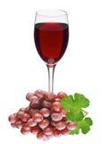 Vidrio del vino rojo y de la uva roja con las hojas verdes Imagenes de archivo