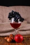 Vidrio del vino rojo y de la uva sobre negro Fotos de archivo