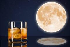 Vidrio del whisky en el cielo de medianoche con el fondo de la Luna Llena Foto de archivo