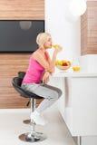 Vidrio del zumo de naranja de la bebida de la mujer en su cocina Imagenes de archivo