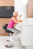 Vidrio del zumo de naranja de la bebida de la mujer en su cocina Fotografía de archivo