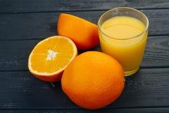 Vidrio del zumo de naranja y de la naranja en fondo gris Foto de archivo