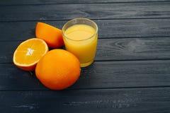 Vidrio del zumo de naranja y de la naranja en fondo gris Imagen de archivo