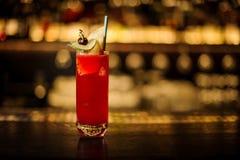 Vidrio elegante de la bebida jugosa dulce roja en un vidrio de cóctel con la fruta imagenes de archivo