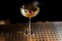 Vidrio elegante llenado del cóctel dulce sabroso adornado con el brote color de rosa imagen de archivo libre de regalías