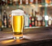 Vidrio escarchado de cerveza ligera en el contador de la barra fotos de archivo