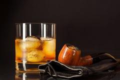 Vidrio escocés de la bebida y tubo que fuma en fondo negro Foto de archivo