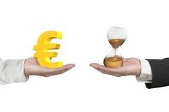 Vidrio euro del símbolo y de la hora con dos manos Foto de archivo libre de regalías