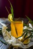 Vidrio figurado de zumo de fruta amarillo con una rebanada de limón y de GR fotos de archivo