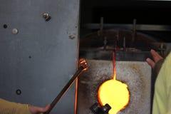 Vidrio fundido en una barra de metal en un horno para la macro que sopla de cristal Fotografía de archivo