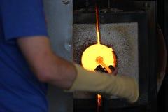 Vidrio fundido en una barra de metal en un horno para la macro que sopla de cristal Imagen de archivo