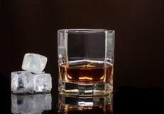 Vidrio hexagonal de whisky con hielo en un fondo oscuro y varios cubos de hielo reales fotos de archivo libres de regalías