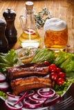 Vidrio lleno de cerveza con una espuma que fluye y de costillas de cerdo cocidas con las verduras en una tabla de madera Imagenes de archivo