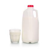 Vidrio lleno de leche por la botella plástica en blanco Fotografía de archivo