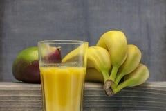 Vidrio orgánico del mango del smoothie y del jugo de los plátanos en la madera imagen de archivo libre de regalías